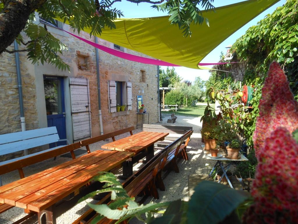 Les tables de jardin sous les voiles d'ombrage du gite de groupe