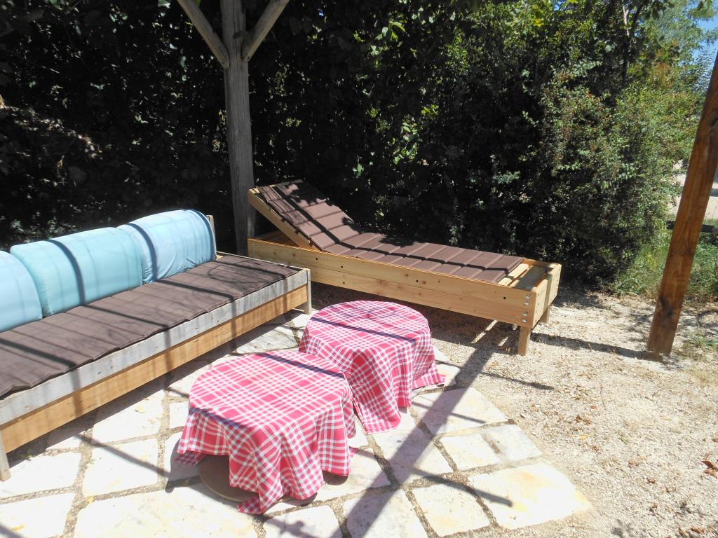 Profitez du salon de jardin du gite de groupe : une banquette et un bain de soleil sous la pergola.